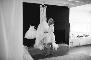 Black and white image of bride standing next to her wedding dress on hanger