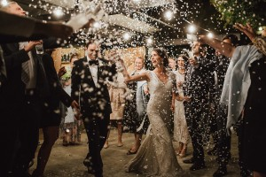 Image of newlyweds leaving wedding reception under confetti archway