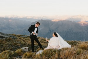 Image of newlyweds on their wedding day amongst long grass in a beautiful mountain landscape